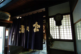 "The interior of the sake brewery Imada Shuzo with the famous curtain ""noren"""