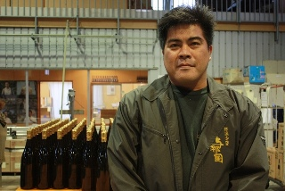 A portrait of Mr. Sakimoto posing with bottles of awamori in his distillery