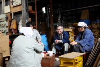 Koshinohana Shuzo Sake brewery workers sit for a break, drinking warm tea
